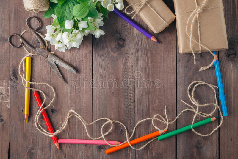 Pen and flowers over wooden background. Top view with copy space stock image
