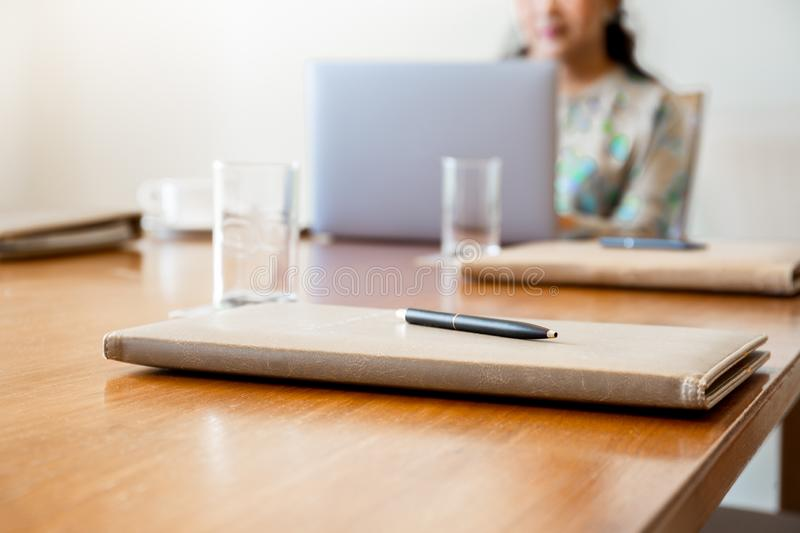 Pen on folder with businesswoman and laptop on meeting desk. royalty free stock images