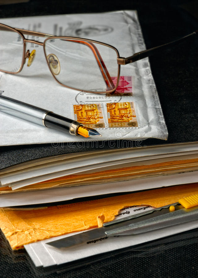 Pen and glasses atop of an envelope stock photo