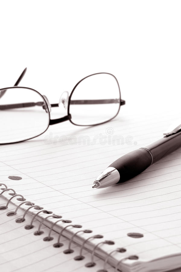 Pen and Glasses on Notebook Blank Paper Sheet royalty free stock photo