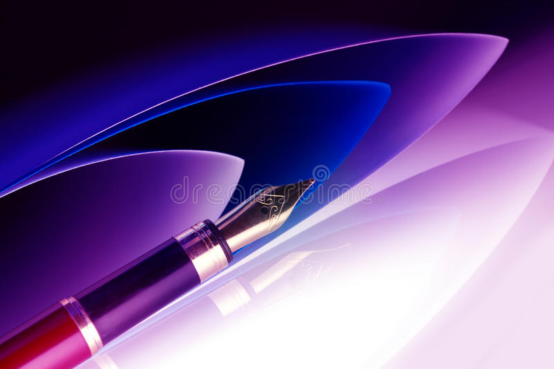 Pen with golden nib. With papers in the background royalty free stock images