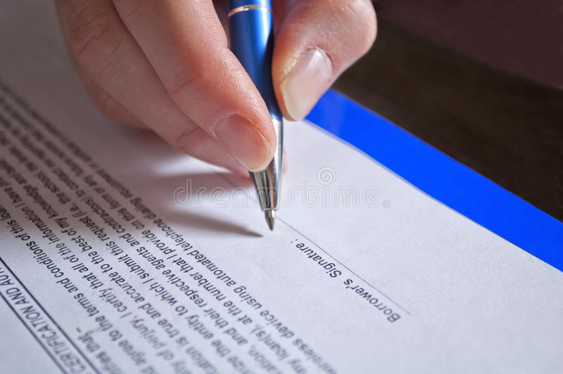 Pen in hand. Concept of signing loan agreement with pen in hand stock image