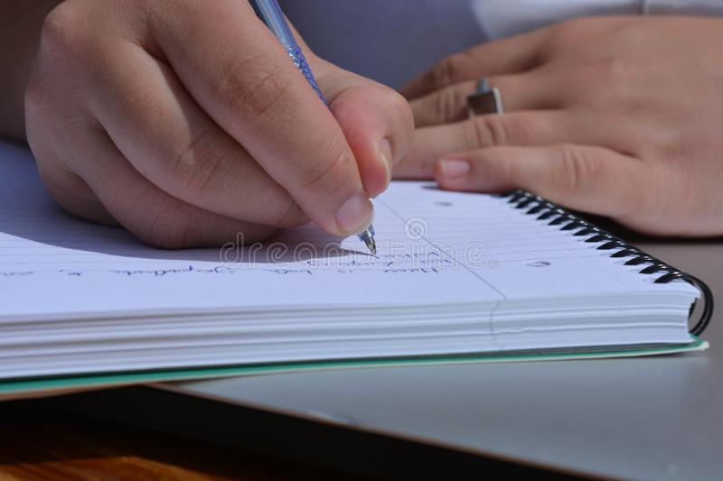 Pen in hand, woman writing in a spiral bound notebook stock image