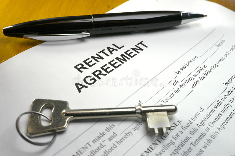Pen and key on rental agreement. Black pen and silver key on a rental agreement royalty free stock photography