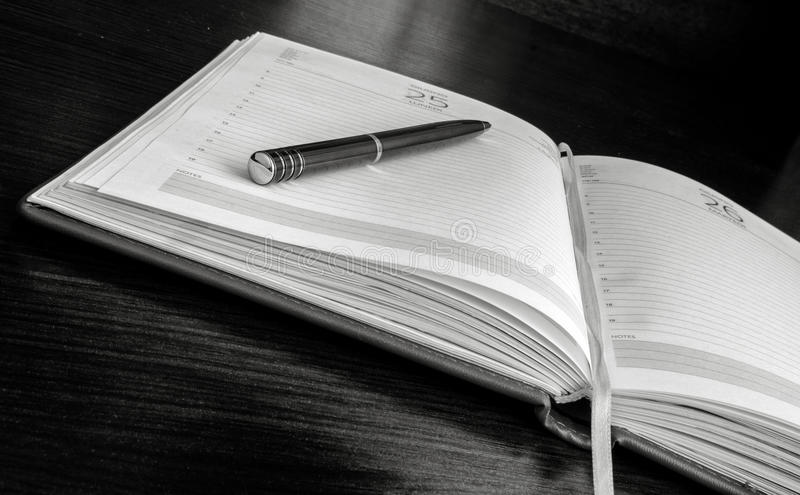 The pen lies on open blank pages of an organizer. Indoors. Horizontal forms. Black-and-white. Photo stock image