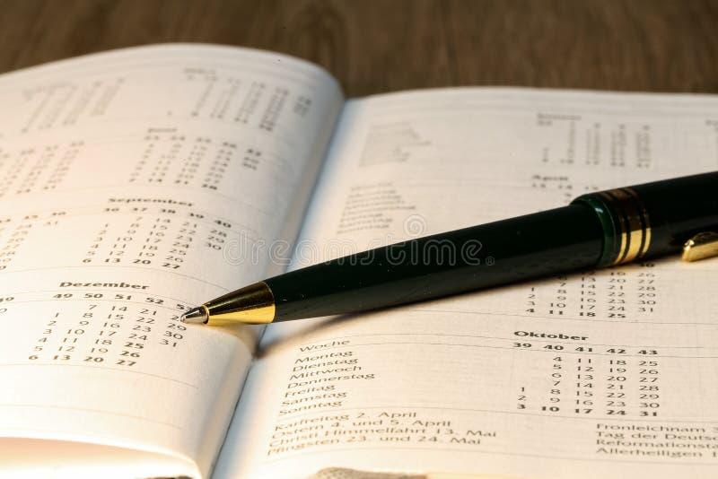 Pen lying on calendar or organizer on desk in office stock image