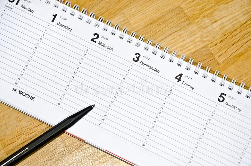 Pen lying on schedule with the days of the week in German. On a wooden desk royalty free stock image