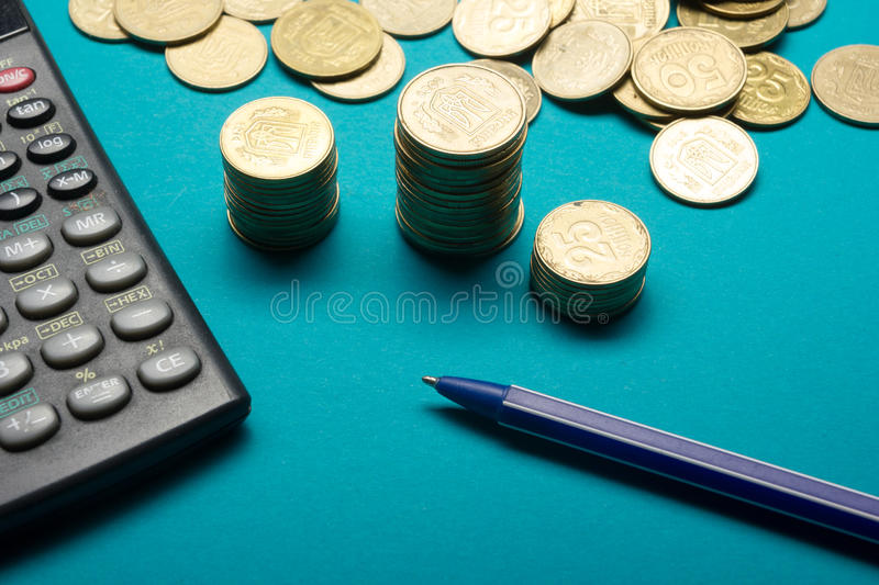 Pen, Money coins stack and calculator for finance concept royalty free stock photo