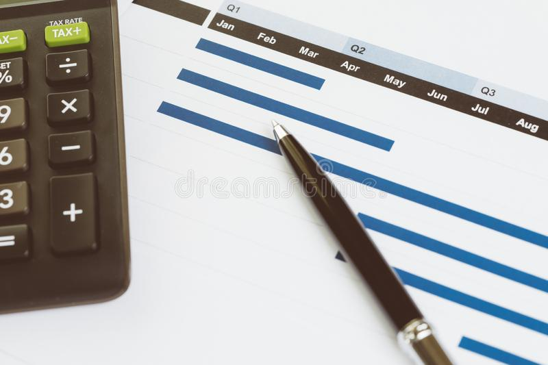 Pen on monthly graph and chart with black calculator on office table using as company profit and loss, financial and accounting royalty free stock photography