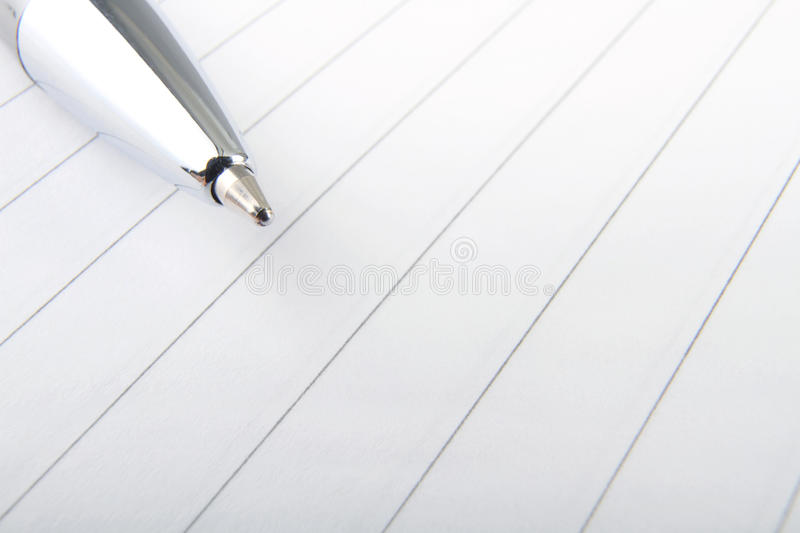 Pen and note paper. Close-up of lined notepad page with ball point pen and copy space stock image