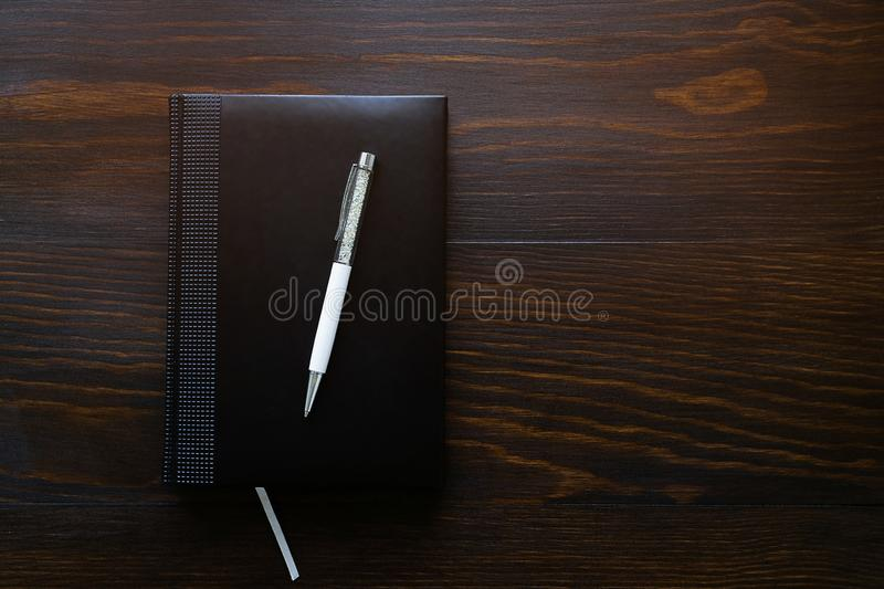Pen, notebook or diary on a wooden table. Free space for text. The concept of office, education, business, making a plan for the stock image