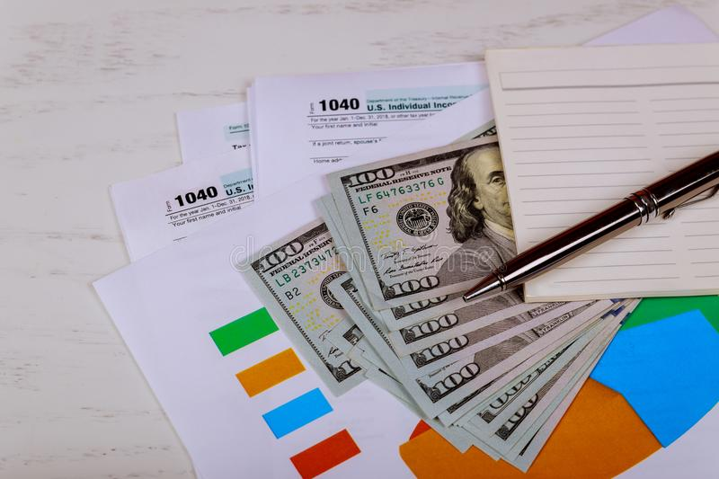 The pen, notebook and dollar bills is lies on the tax form 1040 U.S. Individual Income Tax Return. The time to pay taxes The pen, notebook and dollar bills is royalty free stock photography