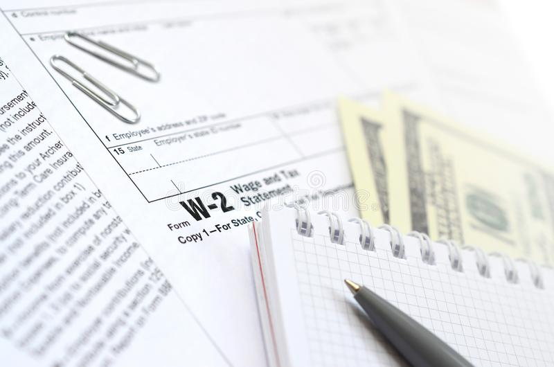 The pen, notebook and dollar bills is lies on the tax form W-2 W. Age and Tax Statement. The time to pay taxes royalty free stock photography