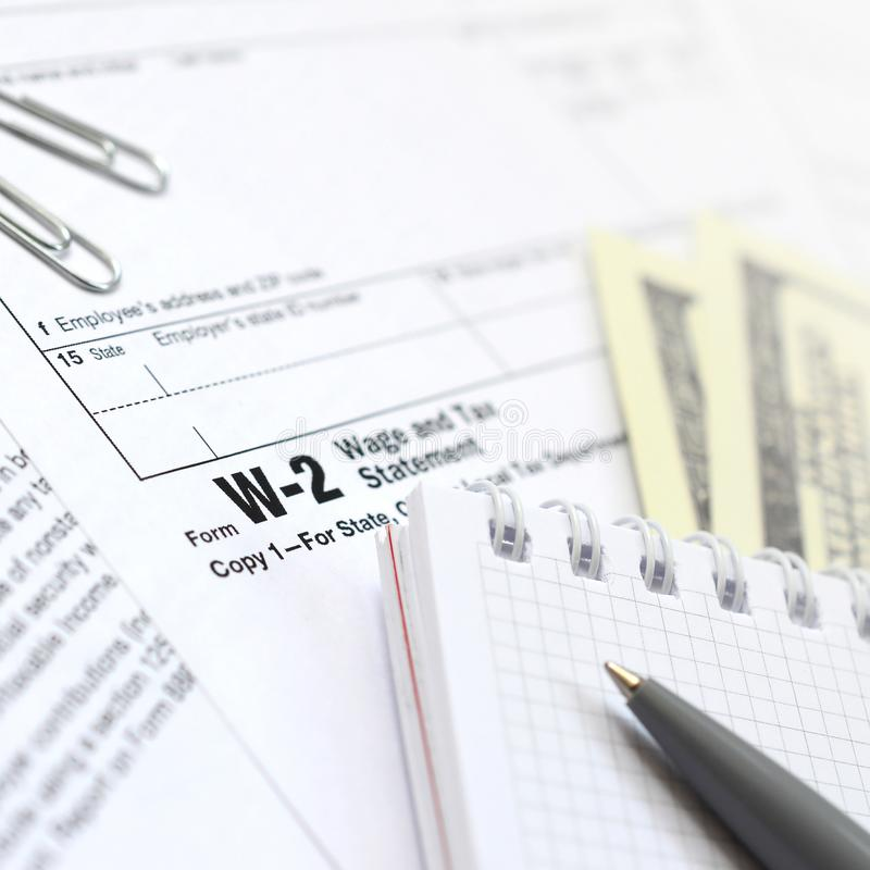 The pen, notebook and dollar bills is lies on the tax form W-2 W. Age and Tax Statement. The time to pay taxes royalty free stock image