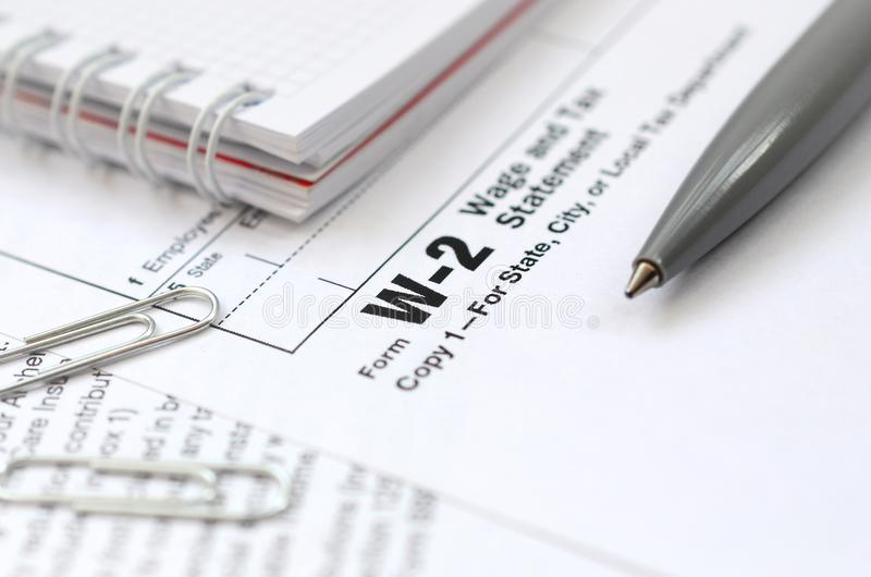 The pen and notebook on the tax form W-2 Wage and Tax Statement. The time to pay taxes stock photo