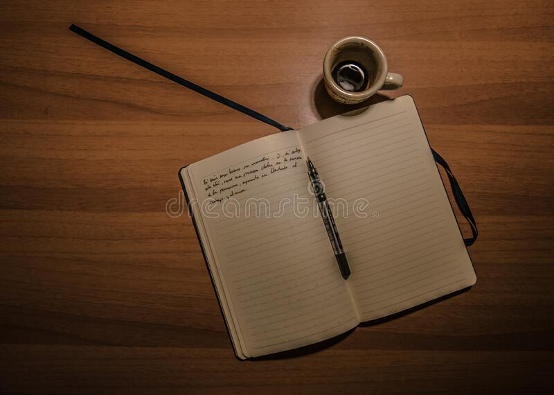 Pen on Notebook Beside a Teacup on Brown Wooden Plank royalty free stock photography