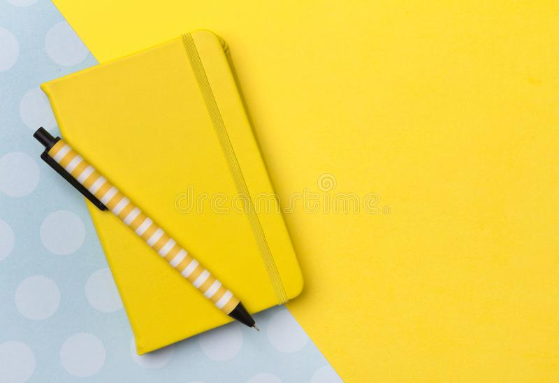 Pen and notepad at yellow turquoise creative background with copy space royalty free stock photography
