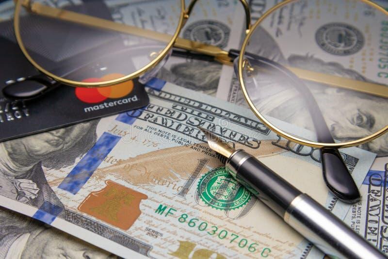 Pen, oogglazen en grafieken de glazen en een Mastercard-kaart zijn op dollars Cheboksary, Rusland, 11/25/2018 royalty-vrije stock fotografie