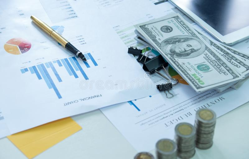 Pen op het document van de financiëngrafiek met muntstukken en dollars royalty-vrije stock fotografie