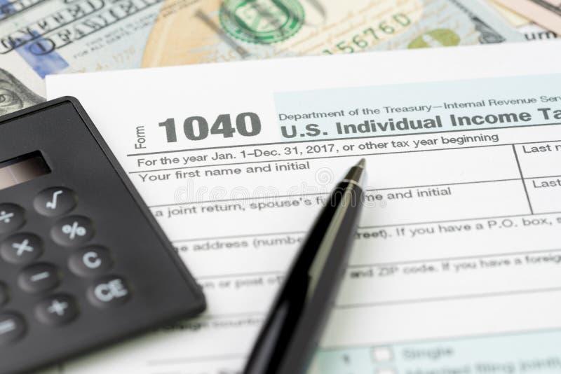Pen op individuele de inkomstenbelastings vullende vorm van de 1040 V.S. met zwarte calculator en Amerikaanse dollarrekening, bel royalty-vrije stock afbeeldingen