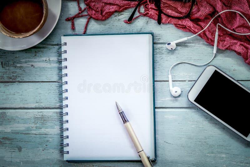 Pen op notitieboekje, cellphone, oortelefoon en koffie stock afbeelding