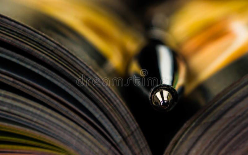 Pen on a opened book. Macro image. library, education,. Pen on a opened book. Macro image. library, education literature a surge of knowledge stock image