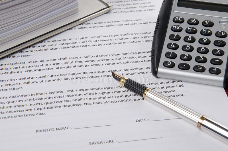 Pen on a paper to sign. With a ring binder an a calculator royalty free stock images