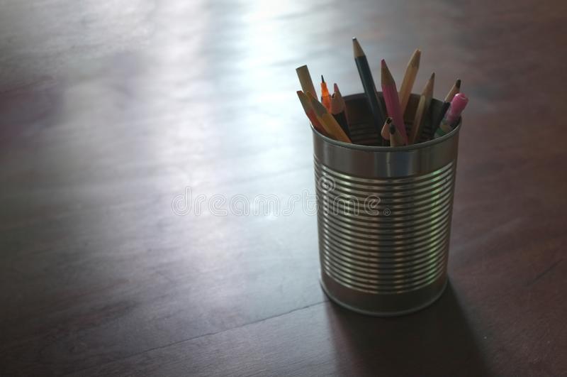 Pen and pencils in tin can, wood table , Concept Back to school.  stock photography