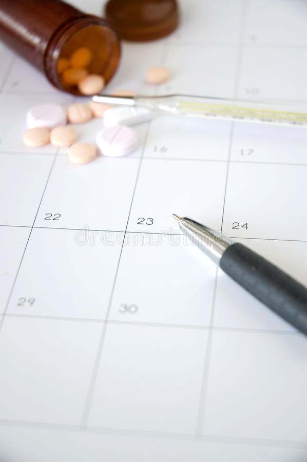 Pen point to date with pills on background. Pen point to date on schedule with pills and thermometer on background stock images
