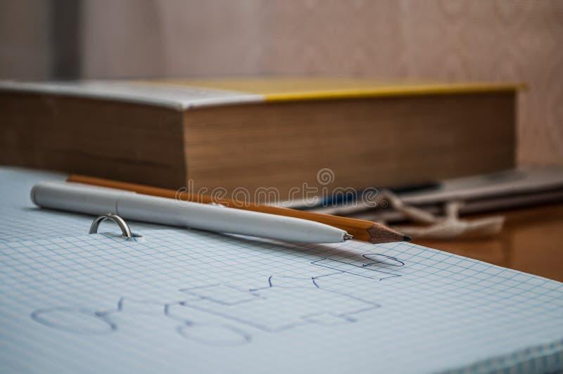Pen, potlood, boek en notitieboekje die op het bureau liggen stock foto