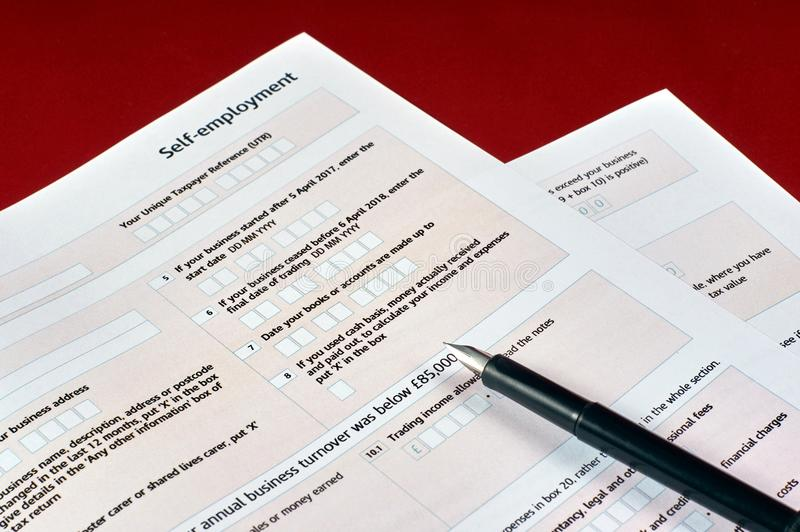 Self employment tax form. Pen and self employment tax form on red velvet background stock photo