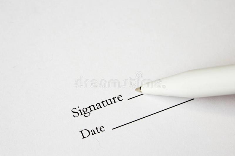 Pen with signature and document in background. Focus on tip of fountain pen nib royalty free stock images