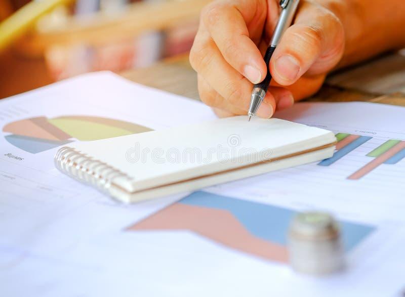 Pen ter beschikking op notitieboekjes met muntstukken worden geplaatst die op stock fotografie