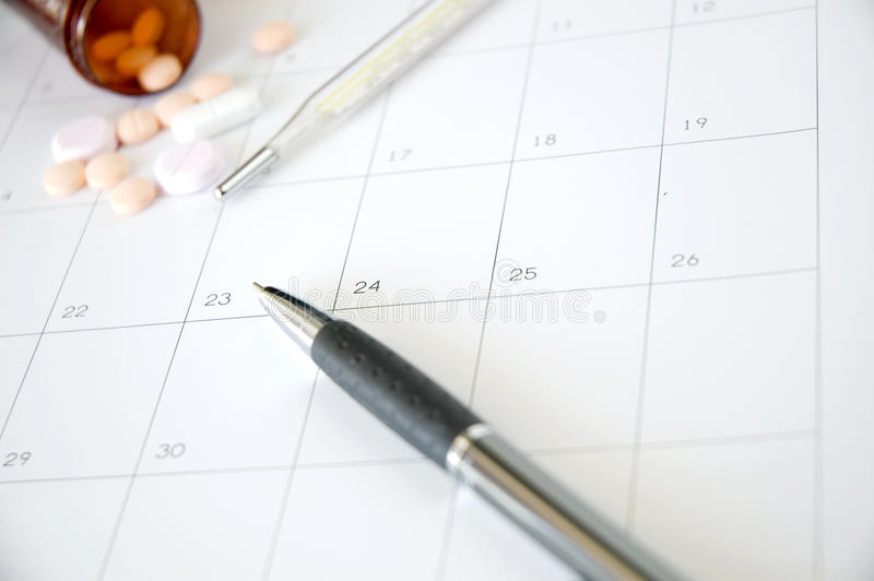 Pen and thermometer on schedule. With pills on background royalty free stock photos