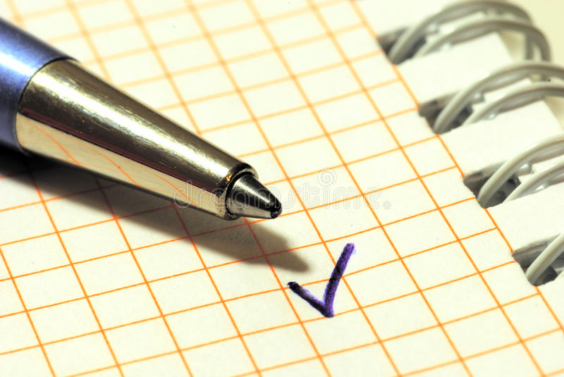 A pen and a tick mark. On the sheet of paper stock photo