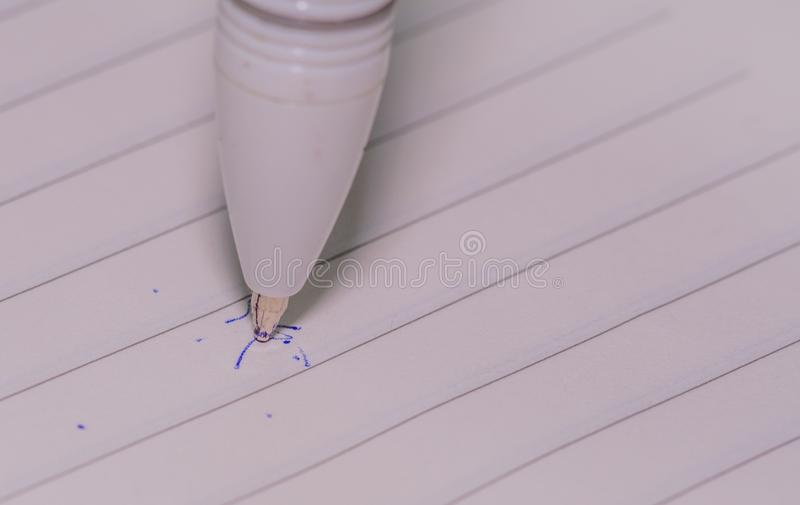 Pen tip on lined white paper stock images