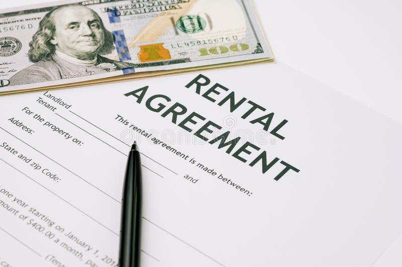 Pen and US Dollar banknotes money on rental agreement form document, ready to sign contract, property or real estate deal between stock photo