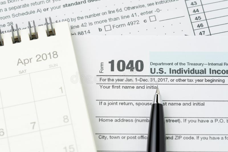 Pen on 1040 US individual income tax filling form with calendar, tax submission or revenue calculation concept stock photos