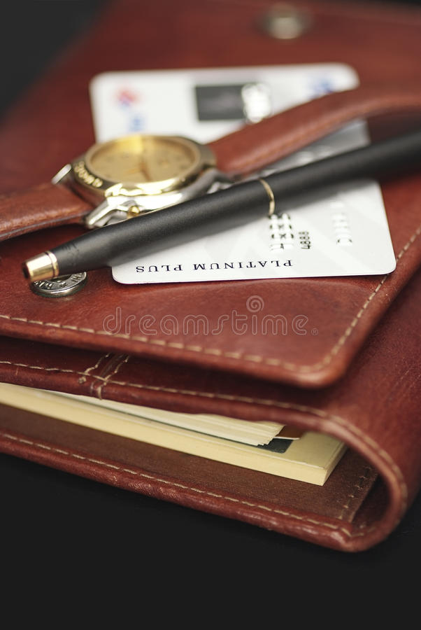 Pen,watch and a credit card on an agenda. Close up of pen,watch and a credit card on an agenda with a black background royalty free stock photography