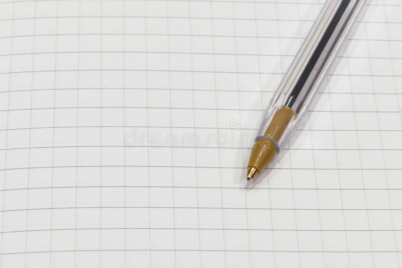 Pen on a white sheet of paper in the cage close up royalty free stock image
