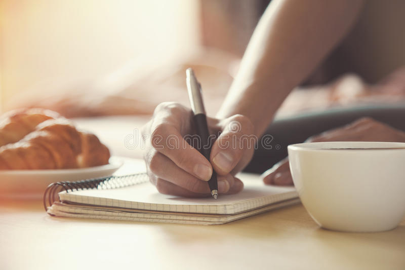 Pen writing on notebook with coffee. Female hands with pen writing on notebook with morning coffee and croissant