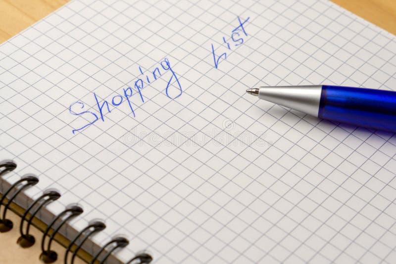 Pena azul em um caderno com folhas em uma gaiola Opinião lateral de lista de compra do sinal fotografia de stock royalty free