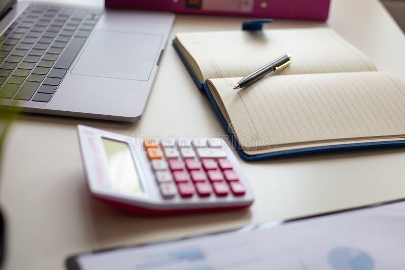 Pena com nota e portátil, calculadora na mesa do aplanamento financeiro foto de stock