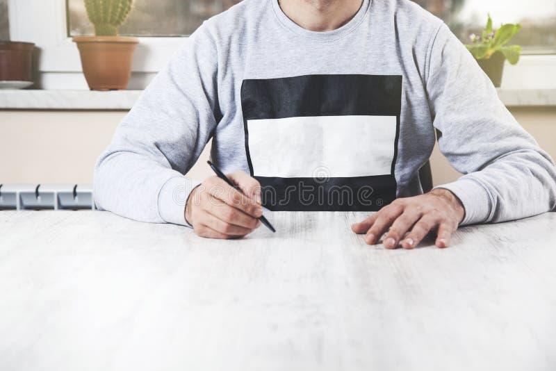 Pena da mão do homem na mesa foto de stock