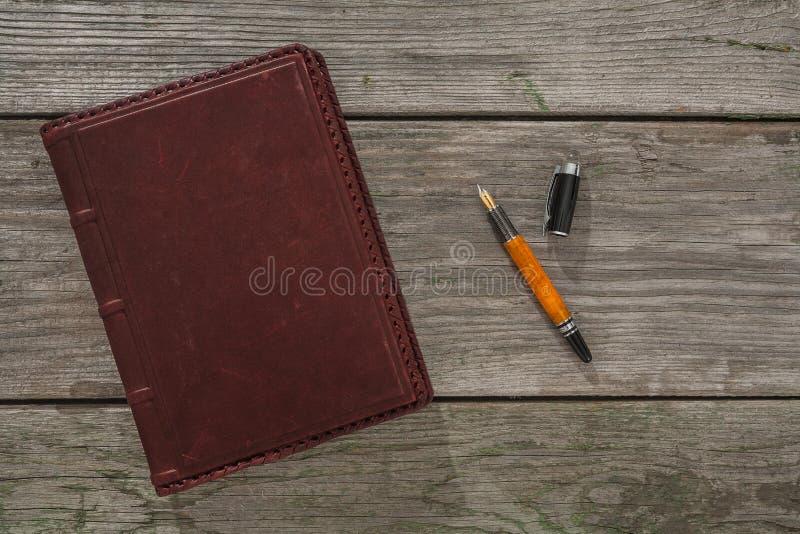 Pena de couro velha do caderno e de fonte em placas de madeira velhas imagem de stock royalty free