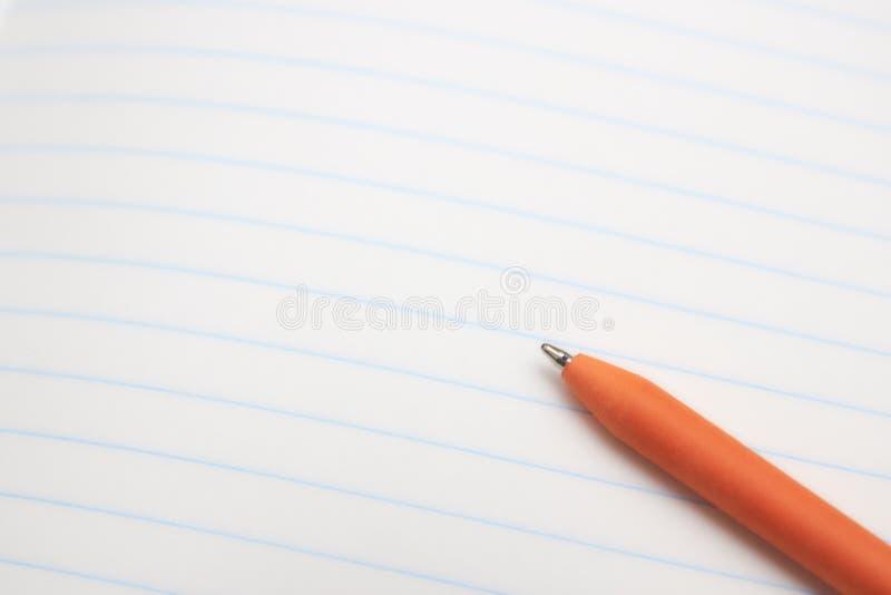 A pena de esferográfica alaranjada encontra-se em uma folha de papel branca o close-up Conceito da instrução Lugar para o texto imagens de stock royalty free