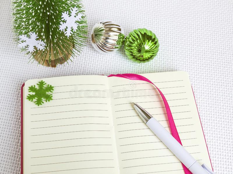 Pena de esferográfica branca no caderno aberto em uma tampa cor-de-rosa e bolas do Natal em um fundo branco, em ideias do Natal e fotos de stock royalty free