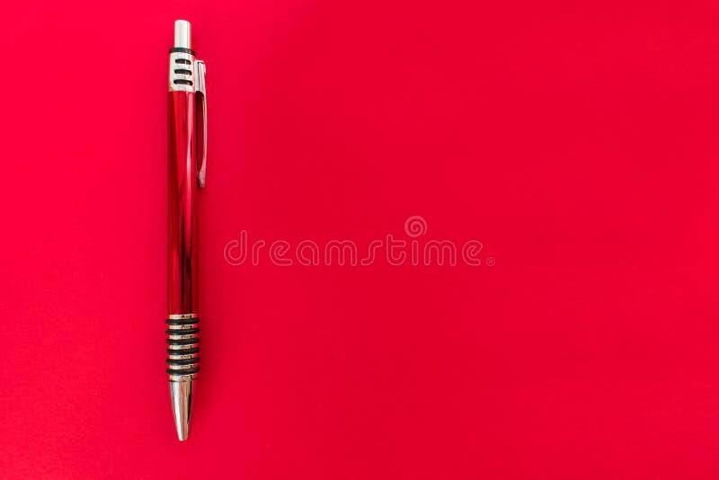 Pena de esferográfica brilhante vermelha no fundo vermelho fotografia de stock royalty free