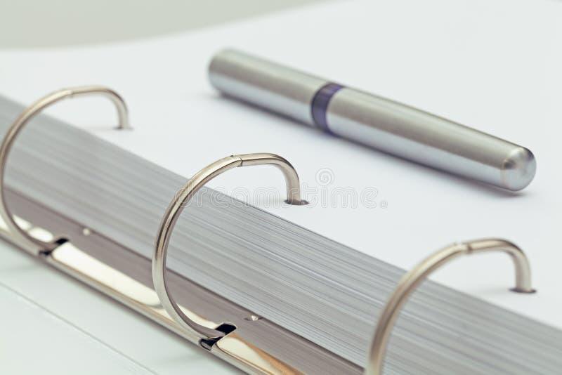 Pena de esferográfica no caderno detalhe do desktop do escritório imagem de stock