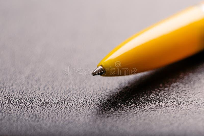 Pena de esferográfica plástica automática amarela com o trajeto de grampeamento no fundo preto Fim acima imagens de stock